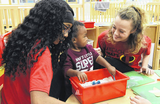 Lima Senior High School's Early Childhood Education students Mikayla Robinson, 16, left, and Claire Mericle, 16, play with J.J. Freeman, 14 months, in a sand box.