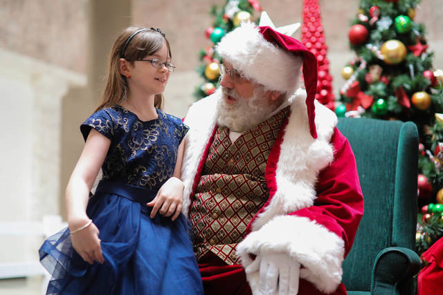 Nine year-old Madelyn Harshbarger of Lima is the lucky child to sit on Santa's lap first during his grand entrance to the Lima Mall on Saturday morning.  Amanda Wilson -The Lima News