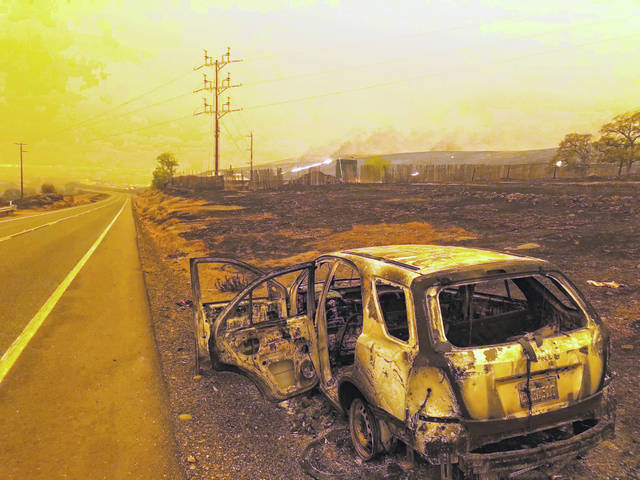 A burned out car sits on the side of the road in Paradise, Calif., Friday, Nov. 9, 2018, after a wildfire swept through the area.
