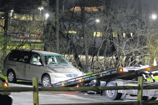 FILE - In this April 10, 2018 file photo, a minivan is removed from the parking lot near the Seven Hills School campus in Cincinnati. Findings and recommendations are coming from two companies hired by Cincinnati authorities for independent reviews into the failed response to Kyle Plush, a 16-year-old student who died trapped in a minivan parked near his school. A special city council meeting is planned Thursday, Nov. 15, for reports on the emergency center and police response.