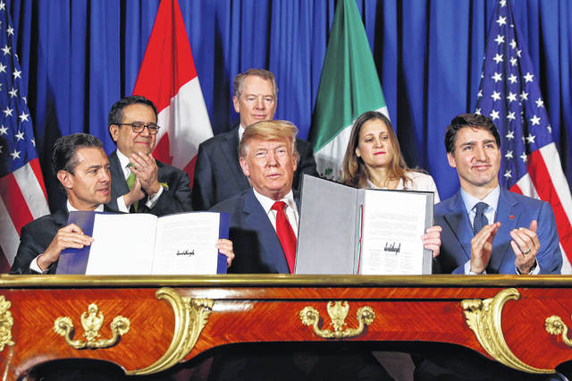 President Donald Trump, Canada's Prime Minister Justin Trudeau, right, and Mexico's President Enrique Pena Neto, left, participate in the USMCA signing ceremony, Friday, Nov. 30, 2018 in Buenos Aires, Argentina.