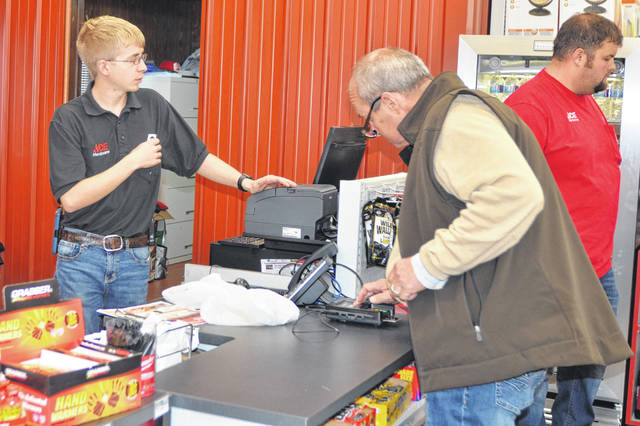 Ace Hardware employee Alex Barden helps a customer Friday at 3720 Elida Road during the grand opening.