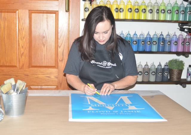Board & Brush co-owner Betsy Lee prepares stencils for a wood sign workshop.