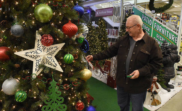 Mike Clum of Elida reads a price tag on a large artificial ornament tree on display at Menards in Lima.
