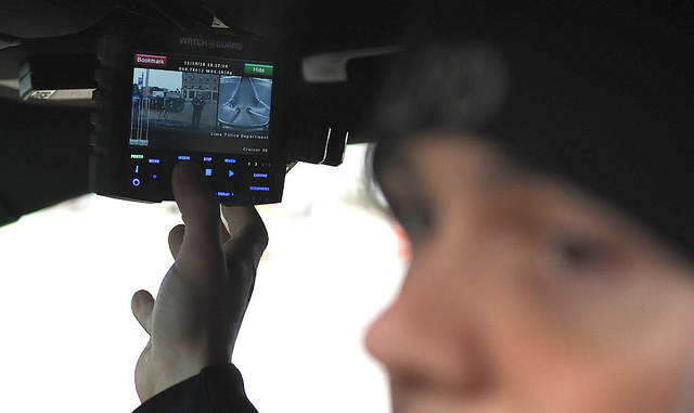 Wearing a new body camera while seated in a police cruiser, Patrolman Justin Halker of the Lima Police Department demonstrates a new Watch Guard in-car video system during a demonstration at the police station Monday morning. Craig J. Orosz | The Lima News