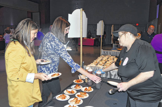 Boots BBQ Manager Lisa Griffith hands out barbecue chicken to Chamberfest attendees Thursday at Veterans Memorial Civic Center, Lima.