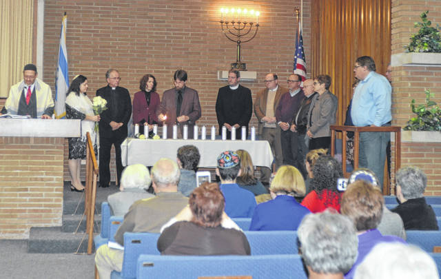 Community members and clergy leaders light candles at Temple Beth Israel-Shaare Zedek during Shabbat Friday evening to remember the lives lost in the violence at Tree of Life Synagogue in Pittsburgh and those who died at the Kroger shooting in Jeffersontown, Kentucky.