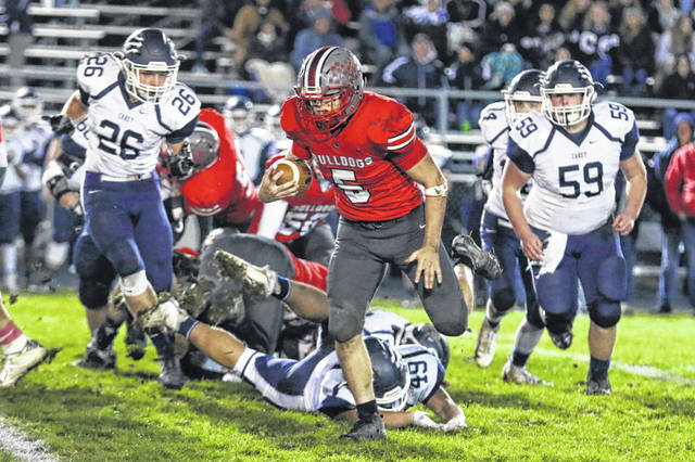 Columbus Grove's Garret Nemire gets past Carey's Adam Hackworth during Friday night's Division VI, Region 22 playoff game at Columbus Grove's Clymer Stadium.