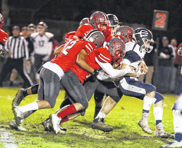 A pack of Columbus Grove defenders stop Carey's Austin Hertel during Friday night's Division VI, Region 22 playoff game at Columbus Grove's Clymer Stadium.