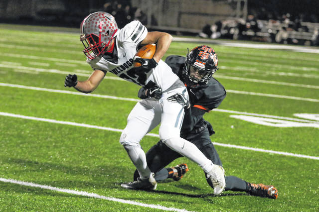Columbus Grove's Caleb Barrientes battles to free of Seneca East's Jacob Siesel of Seneca East during Friday night's Division VI, Regional 22 semifinal at Frost-Kalnow Stadium in Tiffin.