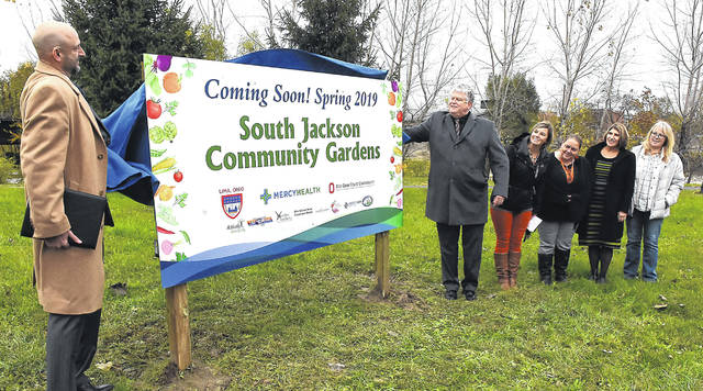 Bob Baxter, CEO of Mercy Health, left, and Jed Metzger president/CEO, Lima Allen County Chamber of Commerce, right, unveil the new South Jackson Community Gardens located on South Jackson Street in Lima on Friday afternoon.