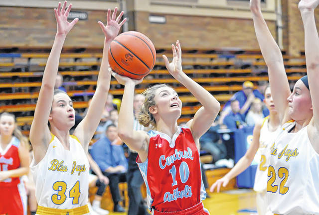 Lima Central Catholic's Sophia Santaguida puts up a shot against Aubrie Friemoth, left, and Betty Vorst of Delphos St. John's during Thursday night's game at Robert A. Arzen Gymnasium in Delphos.