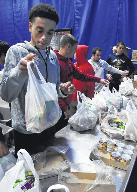 """Sheridan O'Neil, 18, a member of Shawnee basketball team, fills bags of food with teammates and coaches at the West Ohio Food Bank in Lima on Wednesday. The food will be distributed to Shawnee Maplewood students who need additional nutritional support as part of the """"Feed the Tribe"""" program."""