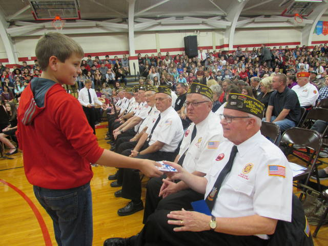 Grant Houser, a 6th-grade student, gives a Veterans Day card to Wapakoneta VFW Post 8445 veterans John Klosterman, left, and Doug Slattery.