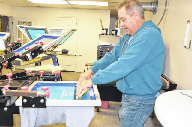 4D Imaging President and CEO Jeff Donley uses his screen press to screen print an image onto a shirt for a customer at his location on 925 N. Jameson Ave., Lima.