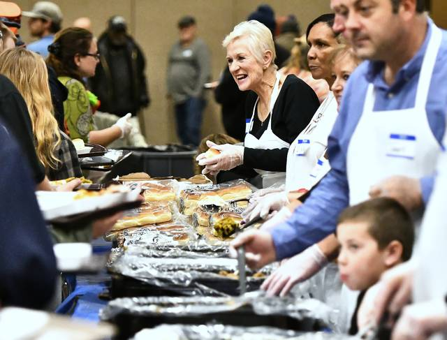 Lima Community Church served food during Thursday's Community Thanksgiving Dinner at the Lima Veterans Memorial Civic and Convention Center.   Richard Parrish | The Lima News