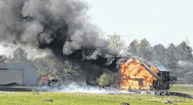 A wind-whipped fire on Sept. 28, 2017, destroys the log home of Jodi and Brian Young at 8201 Reservoir Road in Lafayette. Craig Orosz Photo | The Lima News
