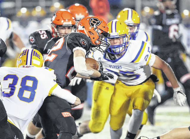 Marion Local's Tanner Ungruhn wraps up Coldwater's Ben Wenning as teammate Brandon Fleck (25) moves in to help with the tackle during Friday night's Division VI, Region 24 final in Sidney.