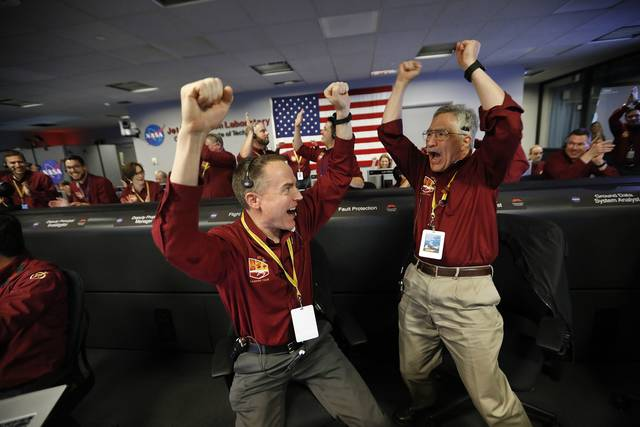 Kris Bruvold, left, Sandy Krasner, right, and the engineers of the flight team react with confirmation of the successful landing of the NASA InSight spacecraft in the Mission Support Area of the Space Flight Operation Facility at JPL in Pasadena Monday.