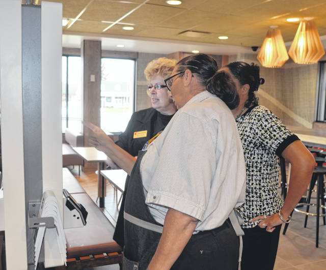 McDonald's Guest Experience Leader Carrie Kohl helps Sheila Custer and Heather Jordan with ordering food off of the menu during the grand opening Thursday of the location on 2455 Shawnee Road.