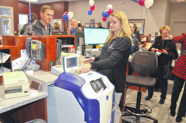 Customer Service Representative Kristen Mullins shows off the new cash recylcer, a device that counts money, prints receipts and withdrawals and deposits money during the re-grand opening Friday of First National Bank on 112 Cherry St., Bluffton.