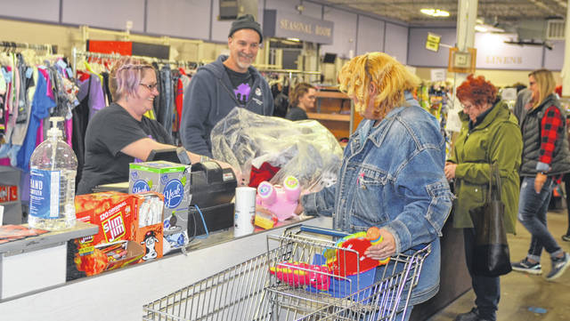 Neighborhood Relief Thrift Store employee Jen Reed helps customer Darcie Hobson with items at 1500 Elida Road.