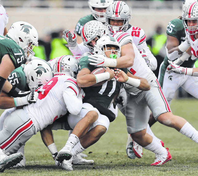 Ohio State's Malik Harrison, left, Brendon White (25) and Tuf Borland combine to stop Michigan State's Conner Heyward during Saturday's game at Spartan Stadium in East Lansing, Mich.