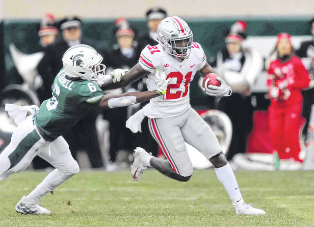 Ohio State's Parris Campbell Jr. applies a stiff arm on Michigan State's Davis Dowell during Saturday's game at Spartan Stadium in East Lansing, Mich.