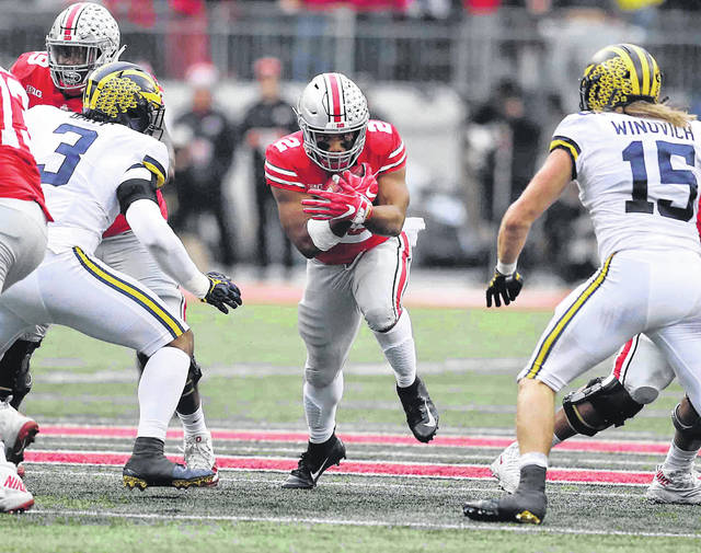 Ohio State's J.K. Dobbins finds a path between Michigan's Rashon Gary (3) and Chase Winovich (15) during Saturday's game at Ohio Stadium in Columbus.