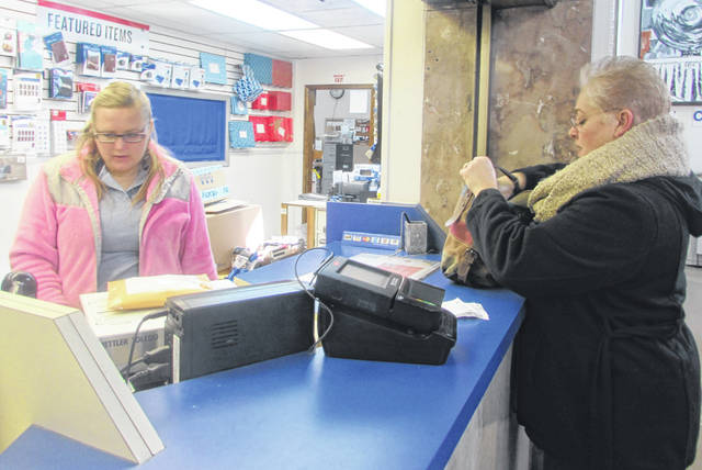 Amy Norway, the lead sales and service clerk at Lima's downtown post office, helps customer Diana Croteau, of Lima, mail out Christmas packages Friday morning.