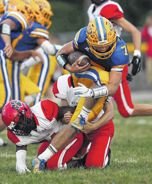 """St. Marys' Sean Perry fights for yardage against Kenton's Malik Jett, left, and Jacob Eversole during a Western Buckeye League game in September at Skip Baughman Stadium in St. Marys. Perry is part of a Roughrider senior class that head coach Doug Frye describes as more leading by example and not so much """"rah rah"""" guys."""