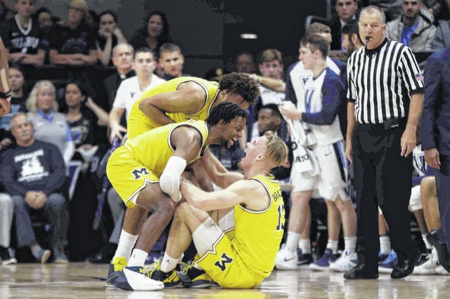 Michigan's Ignas Brazdeikis, right, and Zavier Simpson react after a foul during the first half of an NCAA college basketball game against Villanova, Wednesday, Nov. 14, 2018, in Villanova, Pa. (AP Photo/Matt Slocum)
