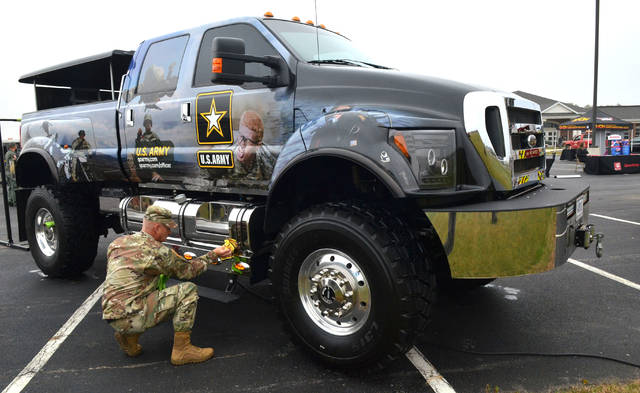 "Sgt. James Heskett of the U.S. Army cleans the ""Army Extreme Truck"" used for recruiting events. The extreme truck is a 2013 Ford F-650 diesel 4x4 on display during the Putnam County Educational Service Center event on Tuesday morning. Craig J. Orosz 