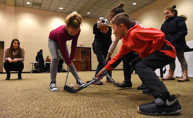 Canadian student, Ally Cumming, far left, of University of Northwestern Ohio watches as Elida Elementary first-grade students play hockey during an International Fair held at UNOH Event Center on Wednesday.