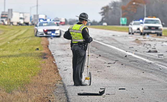 An Ohio State Patrolman surveys the scene of a double-fatal wreck on U.S. 30 near Delphos. Richard Parrish | The Lima News