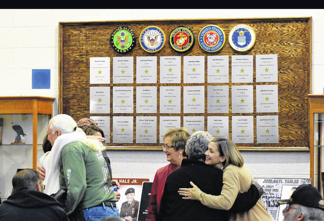 Family members embrace after viewing the new veterans wall before its dedication on Friday at Allen East schools.