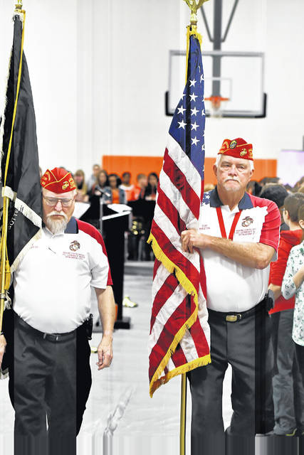 Color guards Steve Montgomery, left, and Tom Martin present the colors during Friday's Veterans Day Recognition Ceremony at Elida Middle School.
