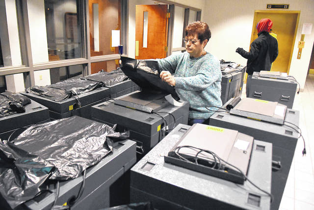 Allen County Board of Elections director, Kathy Meyer, covers ballet machines with plastic bags before being delivered to polling locations throughout the county on Thursday morning. A total of 37 ballet machines will be loaded.