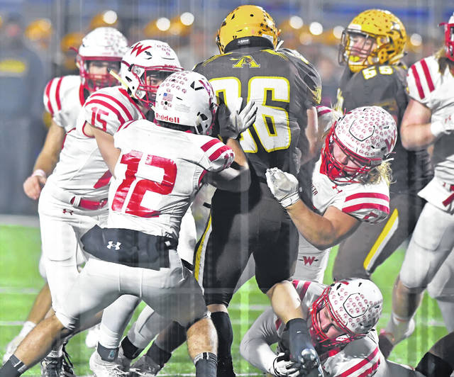 From left, Wapakoneta's Devin Huelskamp, (15), Devin Kuhns (12), Brenan Knueve (56) and Keith Houser (73) tackle Kettering Alter's Peter Riazzi during Friday night's Division III, Region 12 final at Alexander Stadium in Piqua.