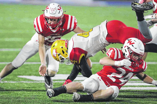 Wapakoneta's Devin Huelskamp, left, and Aaron Chambers tackle Bishop Fenwick's Caleb Davis during Friday night's Division lll, Region 12 semifinal at Alexander Stadium in Piqua.