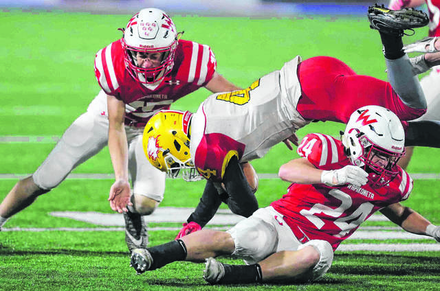 Wapakoneta's Devin Huelskamp, left, and Aaron Chambers tackle Bishop Fenwick's Caleb Davis during Friday night's Division lll, Region 12 at Alexander Stadium in Piqua. Don Speck | The Lima News