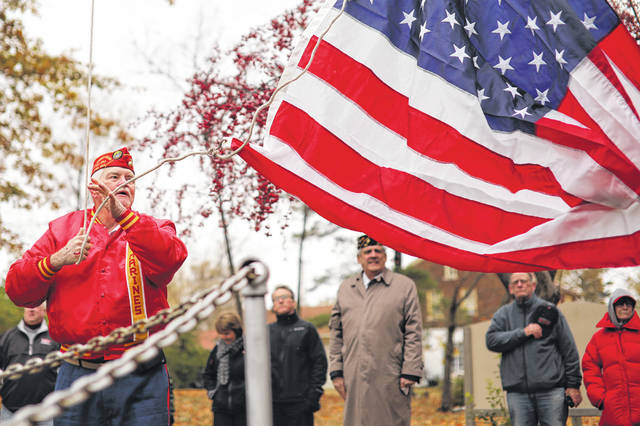 Commandant of Marine Corp Leaugue Thomas Martin raises the flag in a ceremony held at Faurot Park on Saturday morning to commemorate the 100th anniversary of the end of World War I.