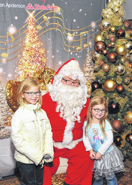 Athena Lutterbeck and Elianna Lutterback sit with Santa Claus during last year's Flip The Switch in downtown Lima.