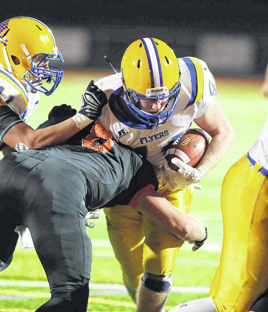 Marion Local's Darrin Hays fights for yardage against Seneca East's Blaine Swartzmiller during Friday night's Division VI state semifinal at Spartan Stadium.