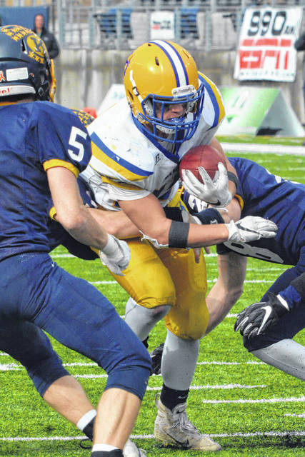 Marion Local's Brandon Fleck battles for yardage during Friday's Division VI state championship game against Kirtland at Tom Benson Stadium in Canton.