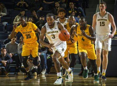 Michigan guard and Lima Senior graduate Xavier Simpson (3) dribbles ahead of Norfolk State guard Derrik Jamerson Jr. (35) and guard Joe Bryant Jr. (4) during Tuesday night's game in Ann Arbor, Mich., (AP photo)