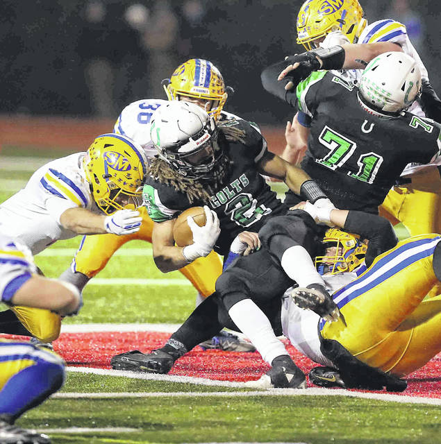 Several members of the St.Marys defense, including Sean Perry, left, and Eddie Fowler (39) stop Clear Fork's Trevon Trammell during last Saturday's Division IV, Region 14 final in Bellefontaine.
