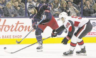 Columbus Blue Jackets' David Savard, left, shoots on goal as Ottawa Senators' Maxime Lajoie defends during the second period of Monday night's game in Columbus (AP Photo)