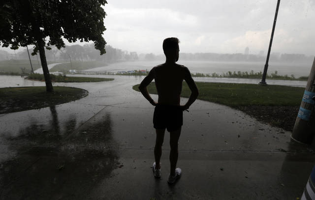"A man takes shelter from a rainstorm while running at Gray's Lake Park in Des Moines in May. Researchers have found dozens of unconscious biases that can drive people to make money decisions they later regret. These behavioral economics concepts include things like ""anchoring,"" when a specific and perhaps arbitrary number you have in mind sways your decision-making. Or, the ""endowment effect"" can cause you to overvalue something simply because you own it, leading you to cling to a stock that's tanking."