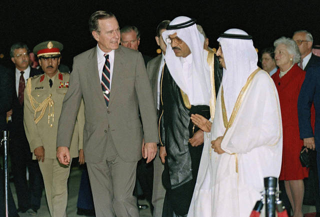 FILE - In this Nov. 21, 1990 file photo, President George H.W. Bush is greeted by King Fahd as he arrives in Saudi Arabia. At right is first lady Barbara Bush. At center is an interpreter. Bush died at the age of 94 on Friday, Nov. 30, 2018, about eight months after the death of his wife, Barbara Bush. (AP Photo/J. Scott Applewhite, File)